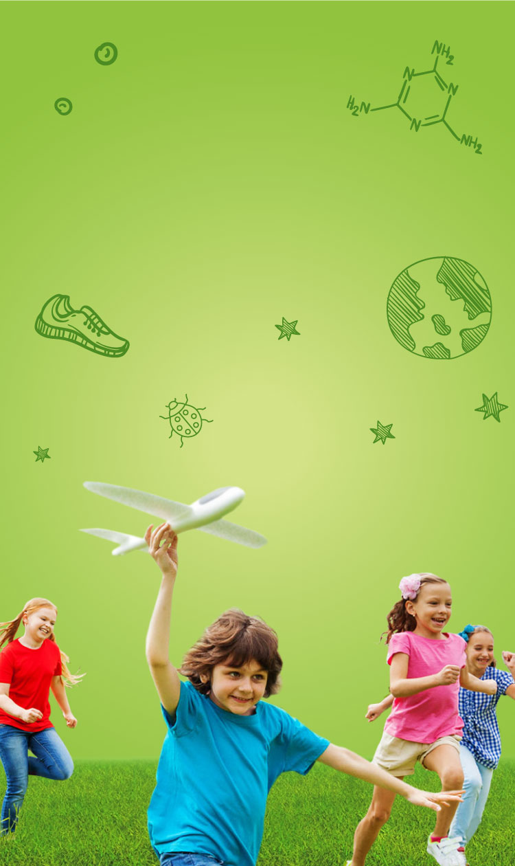 4 children running a green field with a tree in the background.  The child in front is holding a toy plane.